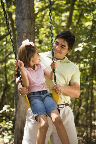 Cute dad and girl swinging