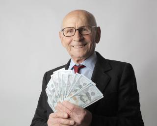 Man-in-black-suit-holding-dollar-bills-3831181